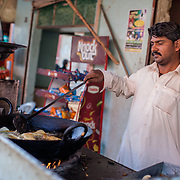 INDIVIDUAL(S) PHOTOGRAPHED: Nazeer Ali. LOCATION: Abdullah Goth, Shah Latif, Bin Qasim Town, Karachi, Pakistan. CAPTION: Wazeer Ali prepares samosas at his shop in Karachi, Pakistan. Now a father of five children, he started out 20 years ago as a helper at various sweet shops, where he learned how to prepare both sweet and savoury delights. In 2008, he started his own sweet shop from a small corner of a retail space in his neighbourhood. After taking his first microfinancing loan of Rs. 50,000 (£350) from the First Micro Finance Bank (FMFB) in 2014, he was able to extend his shop. Since then, over the course of a few cycles of financing, his earnings have risen from Rs. 25,000 to Rs. 80,000 per month. Now, he has his own house near to the shop, and dreams of one day further extending the business by opening branches in other parts of the city.