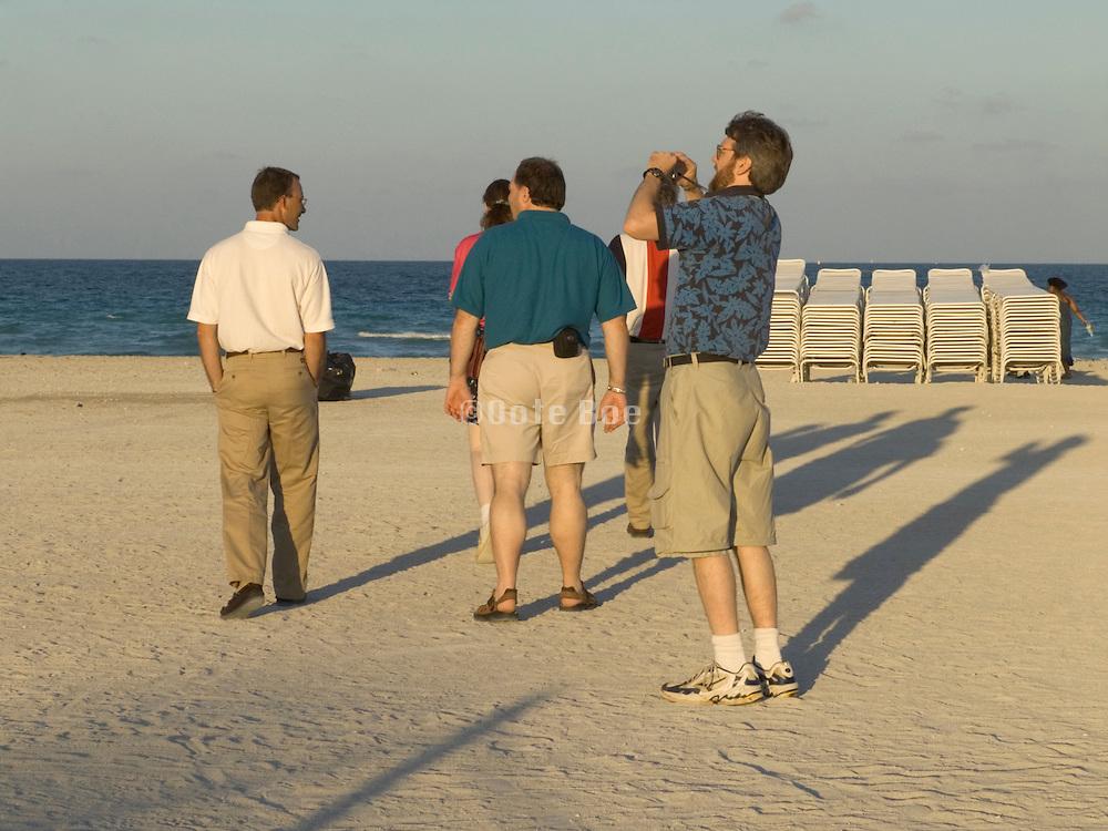 group of tourists walking on to the beach Miami USA