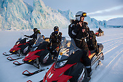 Stephen Jennings (front) and other UNIS students park their snowmobiles on sea ice in Tempelfjorden at the terminus of Tunabreen, Svalbard.