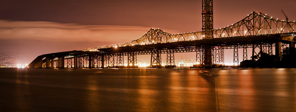The old eastern span of the San Francisco-Oakland bay bridge is seen on an overcast night. The now complete and current eastern span is seen in mid-construction. Photo taken from harbor of Yerba Buena/Treasure island