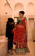 A Hindu bride, Shweta Singhal is being dressed into her jewel encrusted choli and lehenga (blouse & skirt) shortly before the climax of her three day wedding ceremony, Neemrana Fort Palace, Rajasthan India.