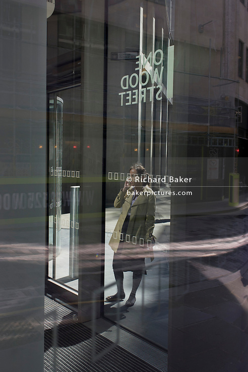 Women use smartphones outside a corporate office entrance with city reflections in glass.