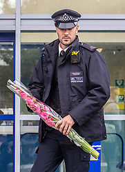 © Licensed to London News Pictures. 25/09/2020. London, UK. Police officers lay flowers outside Croydon Police Station in South London where a custody sergeant was shot dead inside the station last night. The Shooter who turned the gun on himself has survived and was taken to hospital in critical condition. Photo credit: Alex Lentati/LNP