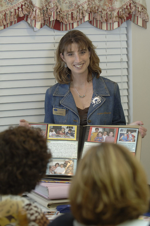 Spring, TX November 5, 2006: Dawn Edens, a consultant for Creative Memories, a home-based business for scrapbook enthusiasts,  explains to her clients the advantages of scrapbooking techniques during a session at her home. ©Bob Daemmrich/