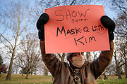 """20 NOVEMBER 2020 - DES MOINES, IOWA: A man holds up a sign critical of Iowa Governor Kim Reynolds' covid response. About 20 people participated in a protest in front of the Iowa Governor's Mansion Friday. They called on Governor Kim Reynolds to immediately issue a comprehensive mask mandate across Iowa. Reynolds, a Republican, has ordered a partial mask mandate that excuses some congregate settings, like classrooms. Iowa has one of the highest per capita COVID-19 infection rates in the country and is dealing with wide """"community spread"""" of the Coronavirus (SARS-CoV-2) throughout the state.        PHOTO BY JACK KURTZ"""