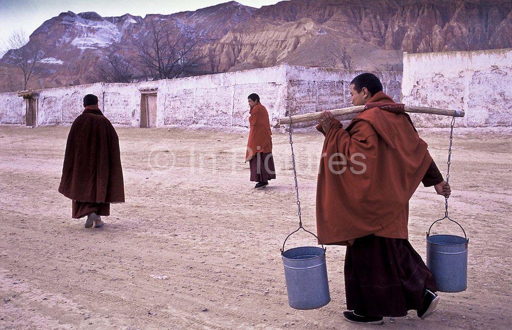 Tibetan buddhist monks collect drinking water from a well inside the monastic complex of Atsog Monastery, deep inside rural Xinghai County, Qinghai province, China