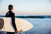 Surfer standing in the water holding his surfboard, looking out at the surf and waves at St Ouen's Bay, Jersey at sunset