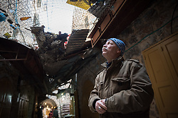 2 March 2020, Hebron: Palestinian shop owner Jamal Marawa looks up towards the Israeli settlement that has been constructed on top of one of the souq streets in the Old City in Hebron, West Bank. Jamal describes how many of his fellow shop owners have been pushed away from what used to be a much more vibrant market street. These days, a metal ceiling collects garbage thrown by the Israeli settlers down onto the Palestinians underneath. Sometimes they even through liquid or wastewater down on the street below, Jamal explains.