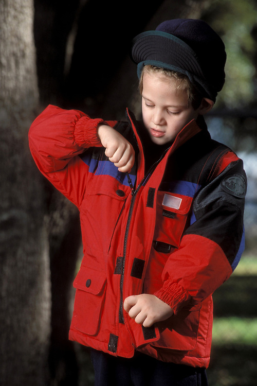 5 year old  Anglo boy zips up warm coat on a autumn day in Austin, Texas.<br /> ©Bob Daemmrich/