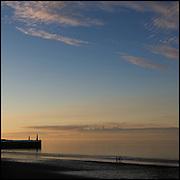 Three people walking on the beach at sunset