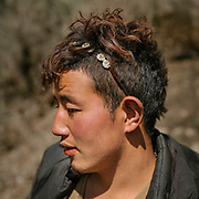 Portrait of a young horse caretaker. From the end of the dirt road, it takes 7 hours to trek up to Laya village.