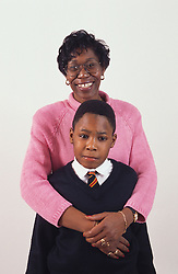 Portrait of mother standing behind son with arms around him; smiling,