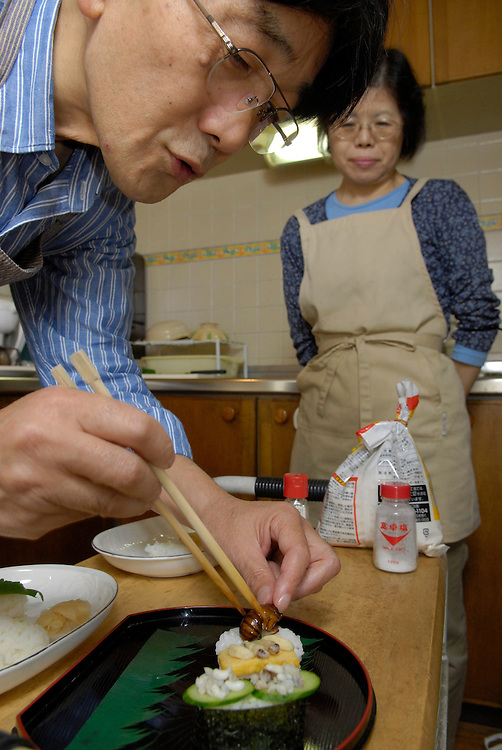 """Shoichi and Chisato Uchiyama preparing insect sushi in their kitchen at home in Tokyo. Tokyo resident Shoichi Uchiyama is the author of """"Fun Insect Cooking"""". His blog on the topic gets 400 hits a day. He believes insects could one day be the solution to food shortages, and that rearing bugs at home could dispel food safety worries."""