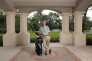 Former Notre Dame and South Carolina head football coach Lou Holtz stands with his golf clubs outside his home in Orlando, Florida.
