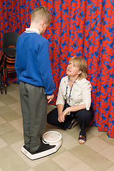 School nurse measuring weight of young boy,