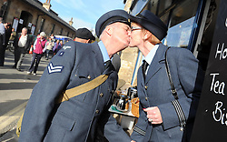 © Licensed to London News Pictures. 11/10/2014. Pickering, UK The annual wartime weekend in Pickering, North Yorkshire. People dress in 1940s period themed outfits and attend parades through the small Yorkshire town which has a traditional steam railway as would have been used in the 1940s. // Pictured: Mark and Diane Lester from Scunthorpe exchange a kiss in at one of the traditional tea shops. Photo credit :  HARRY ATKINSON/LNP