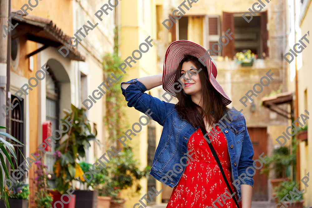 Cheerful pretty woman holding hat and posing at Trastevere in Rome, Italy.