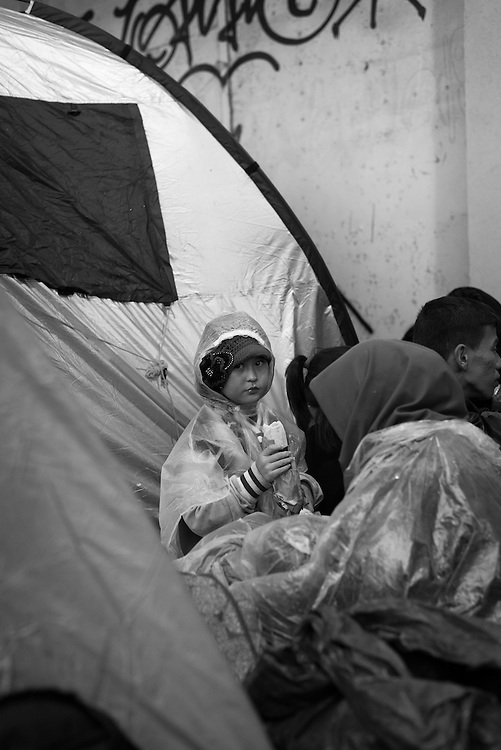 A group of Afghan migrants, including a young girl eating a sandwich, huddle together outside the Customs House building on a rainy night in Mytilene, on the Greek island of Lesbos, while waiting for a ferry to the Greek mainland.