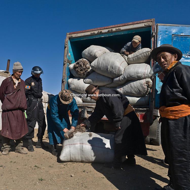 Mongolia. the armed guards of EAGLE security company protect the convoy of  cashmere, the value of a truck full of cashmere wool is more than one million US dollars    -    /   la societe de securite EAGLE avec gardes armes protegent les damions qui parcourent la steppe.  le cachemire brut est vendu 40 $ le kilo , un camion de 40 tonnes represente plus d'un million de dollars   - Mongolie   /