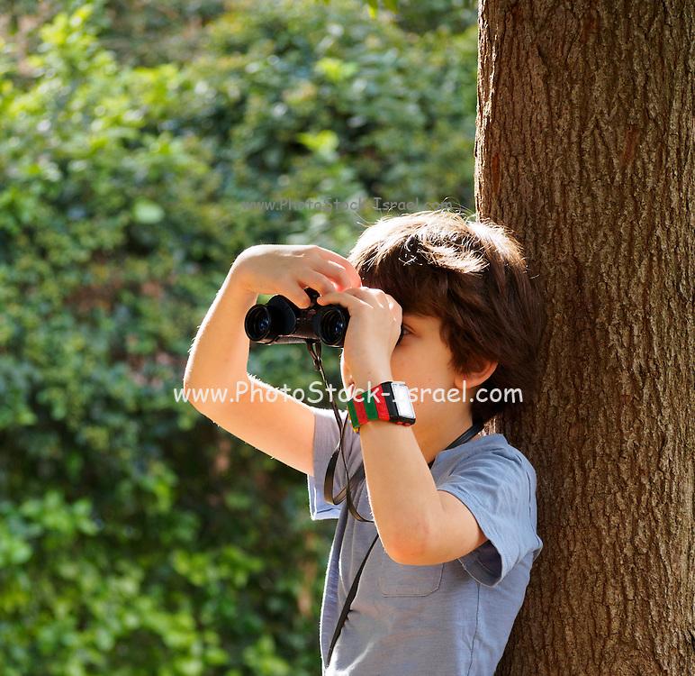 Young birdwatcher a boy of seven with a binoculars