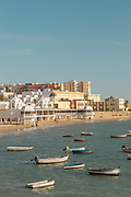 View of boats on sea with beach and city in background, Cadiz, Andalusia, Spain