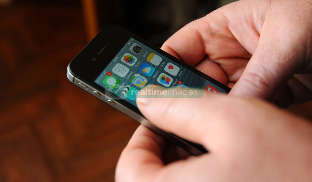 PICTURE POSED BY MODEL A generic stock photo of a man using an Apple iPhone 4s with iOS 8.1 software.