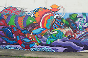A brightly-colored mural of stylized creatures is featured on the exterior wall of of a building in S.E. Portland