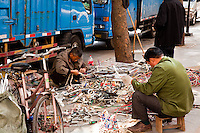 Two men sorting through piles of electronic scaps on the sidewalk in Guangzhou.