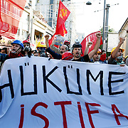 "Protesters holds a banner, reading: ""Government to resign,"" on July 6, 2013 during clashes on Istiklal Avenue in Istanbul. Riot police fired tear gas and water cannon on July 6 to disperse some 3,000 demonstrators who tried to enter flashpoint protest spot Taksim Square in Istanbul. The group had gathered on the Istiklal Avenue pedestrian way that leads to the square, the site of nearly three weeks of protests against Prime Minister Recep Tayyip Erdogan and his Islamic-rooted government that left four people dead and some 8,000 injured. Photo by AYKUT AKICI/TURKPIX"