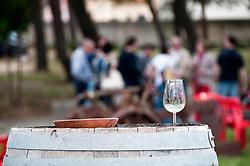 Cutrofiano (Le) - Cantine Aperte 2010 - Masseria L'Astore - Gente visita la masseria. In primo piano un bicchiere di vino rosso posato sopra una botte.