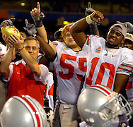 Head coach Jim Tressel, left, holds up the Fiesta Bowl trophy as the game's offensive MVP, quarterback Troy Smith, right, cheers from the awards podium after the game.