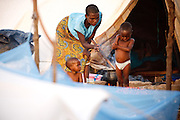 A woman cooks for her family outside the tent where they now live after their home was destroyed by floods in the village of Kpoto, Benin on Tuesday October 26, 2010. Waters have receded in Kpoto, but most of the village was literally flattened by floods that have hit Benin over the past few weeks. Almost all of the village's 1500 people have moved to a location near the local church, located about 500 meters away, where they now live in basic shelters.