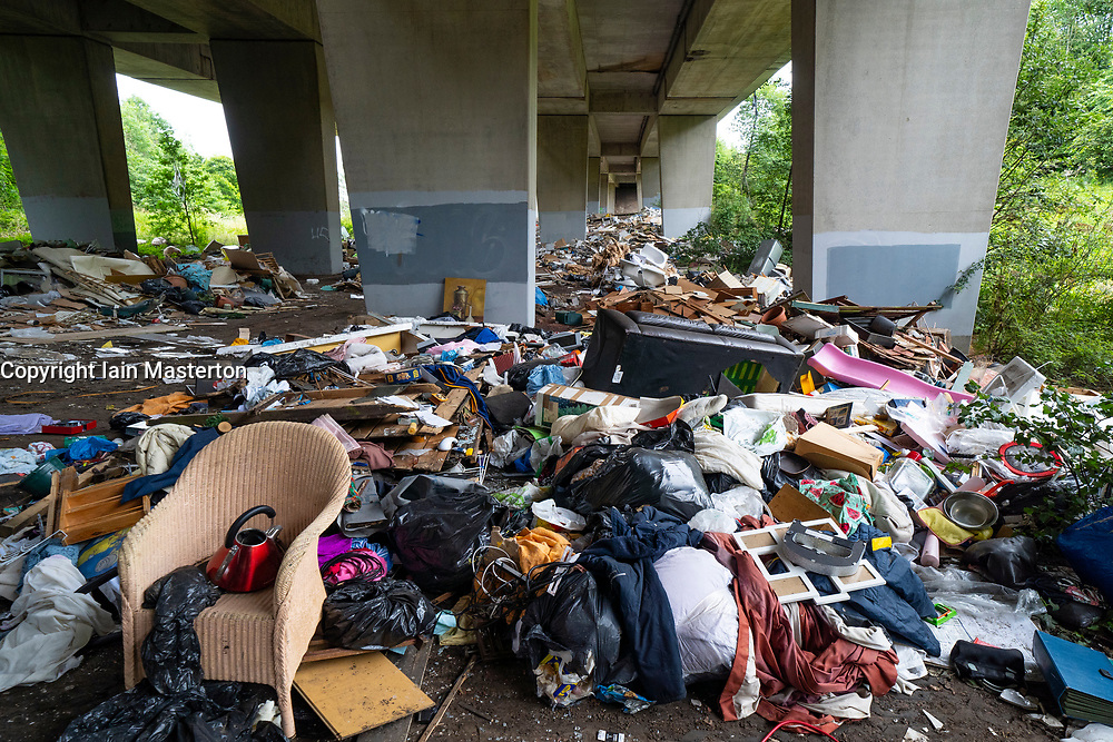 Glasgow, Scotland, UK. 20th August 2021. A huge amount of illegal fly tipping waste from construction sites and households dumped under the M8 viaduct in Blocairn district of Glasgow. Iain Masterton/Alamy Live News