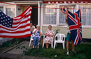 Gathering outside their house in the East End of London, a family sits together to celebrate 50th anniversary of VE (Victory in Europe) Day on 6th May 1995. A man hangs out a Union Jack flag to accompany the Stars and Stripes on a washing line in the front garden. In the week near the anniversary date of May 8, 1945, when the World War II Allies formally accepted the unconditional surrender of the armed forces of Germany and peace was announced to tumultuous crowds across European cities, the British still go out of their way to honour those sacrificed and the realisation that peace was once again achieved. Street parties now – as they did in 1945 – played a large part in the country's patriotic well-being.