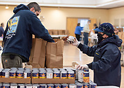 HYANNIS - Kris Clark, Barnstable town councilor, hands canned goods to James Bentley, assistant superintendent of Barnstable's golf operations on Friday, April 3, 2020. The crew was tasked with putting together 240 bags of food to be delivered to seniors.