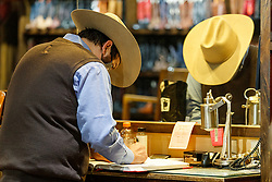 Cowboy recording customer information with boot measurements into leather book at M.L Leddy's Boots, Fort Worth Stockyards National Historic District, Fort Worth, Texas, USA.