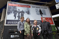 © Licensed to London News Pictures. 23/05/2016. LONDON, UK.  Becky Warnock, Abbie Gillgan, Bethan Lant (all from East End Women's Collective) with Priest-in-Charge of St George-in-the-East church, Angus Ritchie unveil a billboard located opposite the Jack the Ripper museum in Cable Street, Tower Hamlets, advertises a new pop-up museum, 'East-End Women: The Real Story'. Following and opposition and protests against the controversial Jack the Ripper museum, which had promised to celebrate east end women, but activists opposed and claimed glorified violence against women, the museum is a response by the East End Women's Collective, with funding from 38 Degrees members, which aims to celebrate east end women who have stood up for women's rights and against violence. The museum will open at St George-in-the-East church from 26th May to 9th July.  Photo credit: Vickie Flores/LNP