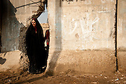 A woman takes a shortcut through a hole in blast walls meant to protect a Shia neighborhood from car bombs.