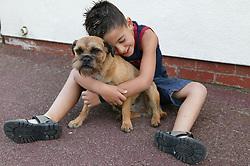 Young boy hugging his pet dog,