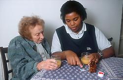 Carer explaining medication to elderly woman,