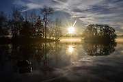 A beautiful sunrise as a double image of Duck Island at right appears on a mirror smooth Green Lake.<br /> <br /> Steve Ringman / The Seattle Times