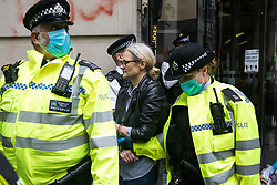Metropolitan Police officers arrest an activist from HS2 Rebellion, an umbrella campaign group comprising longstanding campaigners against the HS2 high-speed rail link as well as Extinction Rebellion activists, who had glued herself to the doors of the Department for Transport during a protest on 4 September 2020 in London, United Kingdom. Activists glued themselves to the doors and pavement outside the building and sprayed fake blood around the entrance during a protest which coincided with an announcement by HS2 Ltd that construction of the controversial £106bn high-speed rail link will now commence.
