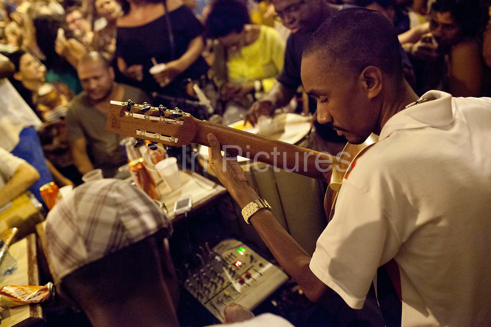 Man playing a guitar, concentrating. Samba musicians playing with crowd around them, Pedra do Sal, the birthplace of Samba, in Gamboa district which was the neighbourhood where the ex slaves lived after abolition, sometimes referred to as the first favela. Rio de Janeiro, Brazil
