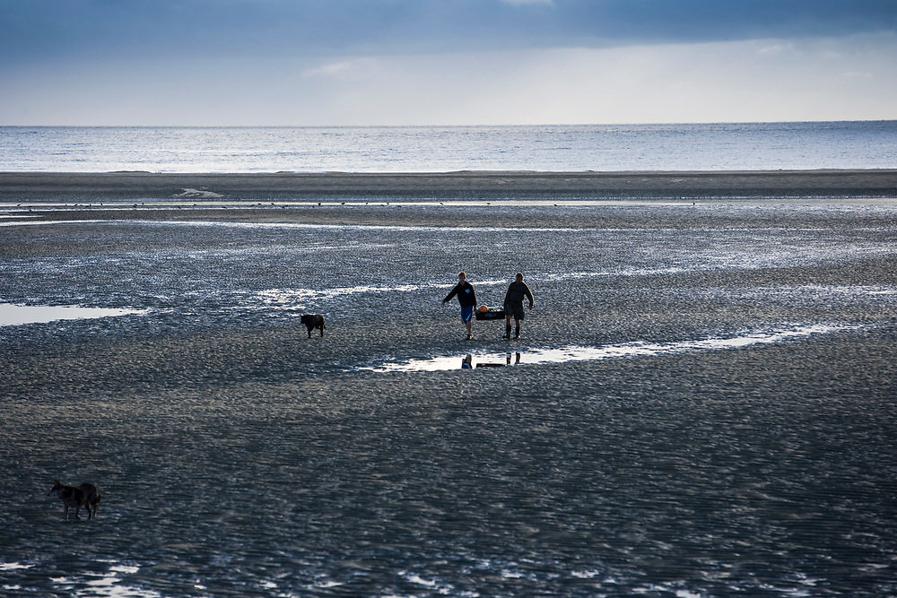 Two people carrying gathered seafood<br /> at low tide from Pakawau Beach, Golden Bay.