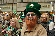 A man in a green hat and fake red beard is among the spectators.