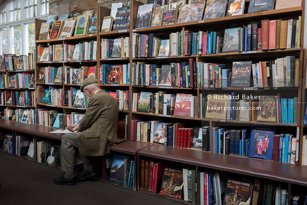 Surrounded by used books is an elderly gentleman reading a title the the shelves of the second-hand bookshop 'Barter Books' in the Northumbrian town of Alnwick, on 26th September 2017, in Alnwick, Northumberland, England.
