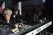 Lunchtime diners in a sunlight window of a London Pret a Manger restaurant.