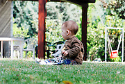 One year old toddler plays in the garden