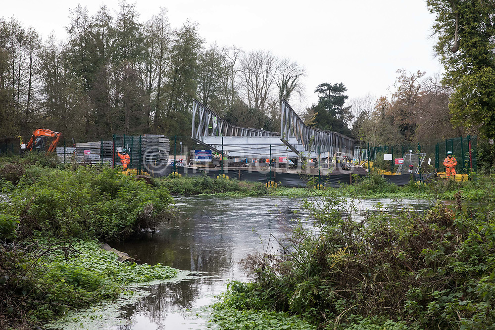 HS2 security guards monitor Bailey bridge building works at Denham Ford in connection with the HS2 high-speed rail link on 24th November 2020 in Denham, United Kingdom. Activists based at Denham Ford Protection Camp on one side of the river Colne continue to oppose the rerouting of pylons through woodland and wetland in Denham Country Park for the controversial high-speed rail project which continues to have huge environmental impact in the Colne Valley.