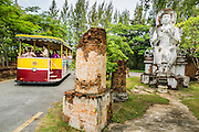 16 JULY 2014 - SAMUT PRAKAN, SAMUT PRAKAN, THAILAND: A shuttle takes a load of students past a statue of an Ayuthaya period Buddha at Ancient Siam. Ancient Siam is a historic park about 200 acres (81 hectares) in size in the city of Samut Prakan, province of Samut Prakan, about 90 minutes from Bangkok. It features historic recreations of important Thai landmarks and is shaped roughly like the country of Thailand.      PHOTO BY JACK KURTZ
